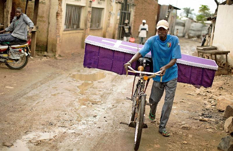 A man pushes his bicycle to deliver a coffin in the Bujumbura suburb of Kanyosha on January 10, 2016 (AFP Photo/Griff Tapper)