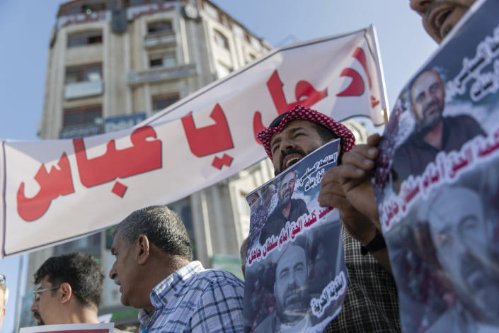 """Demonstrators carry posters with pictures of Palestinian Authority outspoken critic Nizar Banat that reads """"a Martyr of saying the truth in front of an ignorant Sultan,"""" and a banner that reads """"Abbas, leave,"""" during a rally protesting his death, in the West Bank city of Ramallah, Saturday, July 3, 2021. Hundreds of Palestinians gathered to demonstrate against President Mahmoud Abbas, hoping to inject new momentum into a protest movement sparked by the death of an outspoken critic in the custody of security forces. (AP Photo/Nasser Nasser)"""