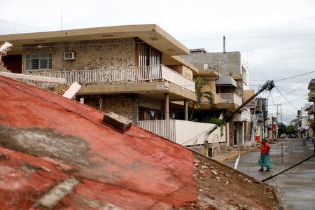 A resident walks near debris and destroyed houses after an earthquake struck the southern coast of Mexico late on Thursday, in Juchitan, Mexico, September 10, 2017. REUTERS/Edgard Garrido