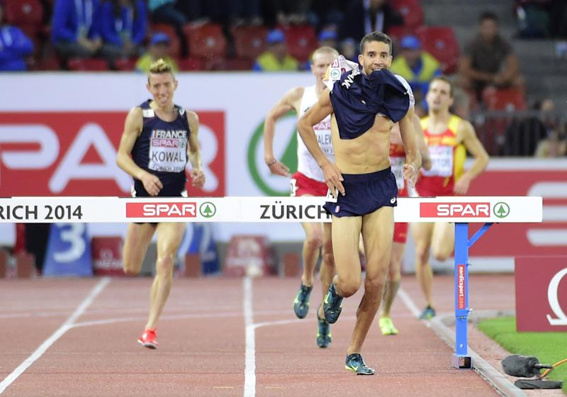 France's Mahiedine Mekhissi-Benabbad (R) runs after removing his jersey, in the last meters of the men's 3000m steeplechase final, during the European Athletics Championships at the Letzigrund stadium in Zurich, on August 14, 2014