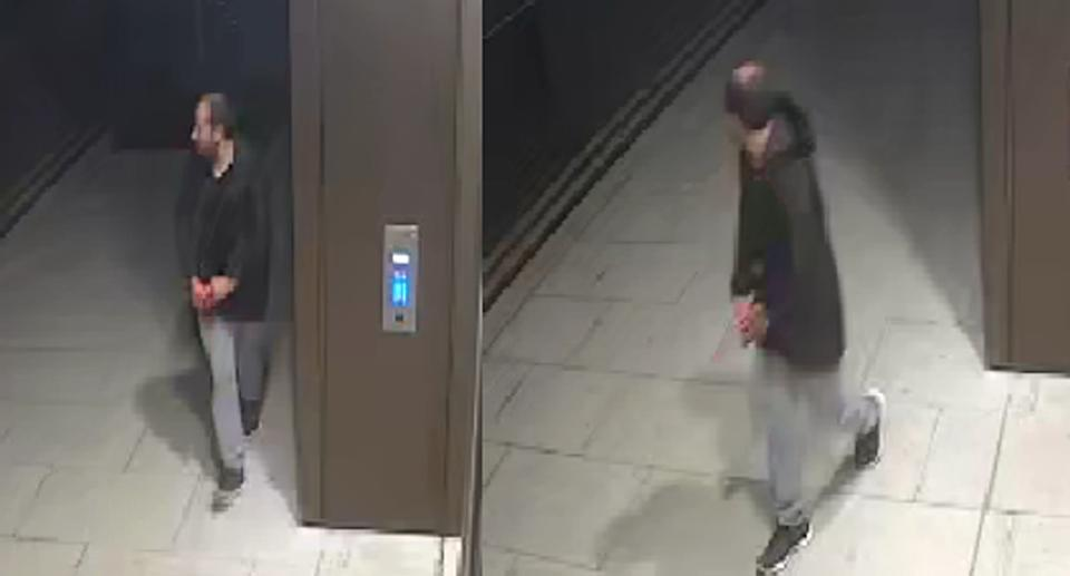 CCTV footage of man looking over his shoulder near a lift wearing light coloured jeans and a black hoodie.
