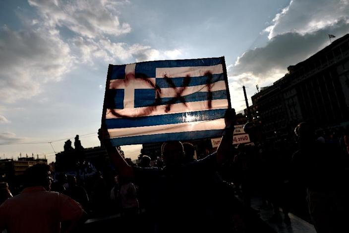 A protester holds a Greek flag with the ''NO'' slogan in reference to the referendum on bailout conditions set by the country's creditors, during a demonstration in front of the Greek parliament in Athens on June 29, 2015 (AFP Photo/Aris Messinis)