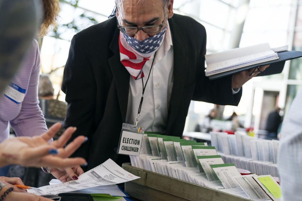 Non-partisan poll election challenger Richard Saad observes election inspectors as they begin to count ballots on Election Day at City Hall in Warren, Mich., in Macomb County, Tuesday, Nov. 3, 2020. (AP Photo/David Goldman)
