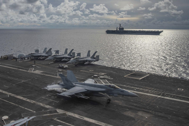 FILE PHOTO: In this photo provided by U.S. Navy, an F/A-18E Super Hornet lands on the flight deck of the USS Ronald Reagan (CVN 76), as USS Nimitz (CVN 68) steams alongside in the South China Sea, Monday, July 6, 2020. (Mass Communication Specialist 2nd Class Samantha Jetzer/U.S. Navy via AP)