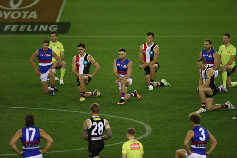 Players kneel during the round 3 AFL match between the St Kilda Saints and the Western Bulldogs.