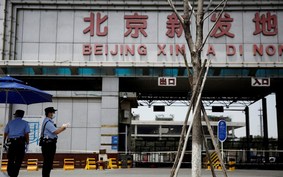 Police officers wearing face masks stand guard outside an entrance to the Xinfadi wholesale market in Beijing - REUTERS