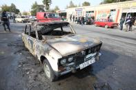 A view shows a burnt car hit by shelling in Barda