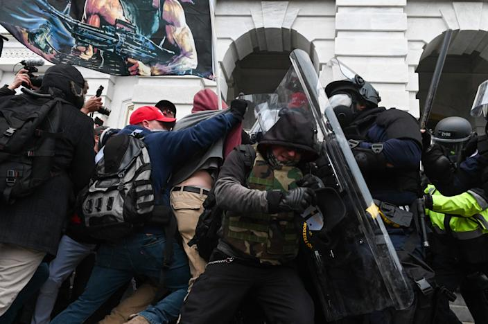 Police push back a crowd of Trump supporters who were rioting at the Capitol building.