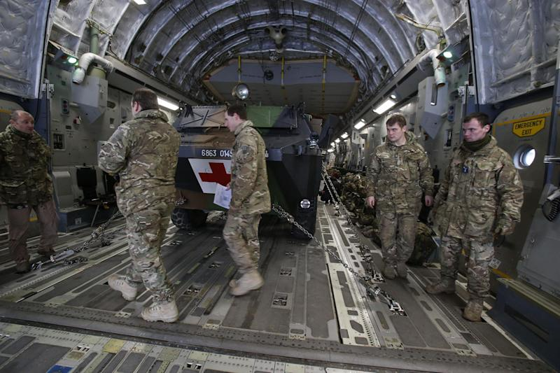 British military personnel walk in front of a French army medical armoured personnel carrier inside a British C17 transport plane at army base in Evreux, 90 kms(56 mls)north of Paris, Monday, Jan. 14, 2013. British military equipment was readied for deployment in Mali on Monday as international intervention in the country increased following advances in the north by Islamic extremists with reported links to Al-Qaida. Two C-17 transport planes have arrived at the French military airbase at Evreux, bound for Mali. Two C-17 transport planes have arrived at the French military airbase at Evreux, bound for Mali. (AP Photo/Michel Euler)