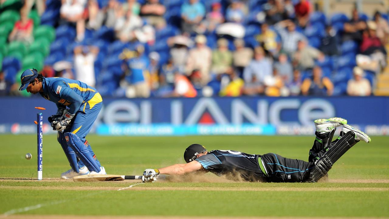 New Zealand's Mitchell McClenaghan dives in to make his ground and score the winning run despite the best efforts of Sri Lanka wicket keeper Kumar Sangakkara during the ICC Champions Trophy match at the SWALEC Stadium, Cardiff.