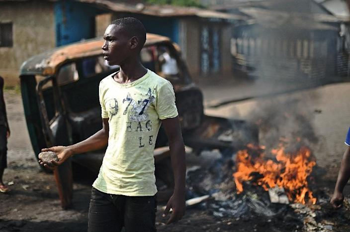 A protestor opposed to Burundian President Pierre Nkurunziza's third term brandishes a rock as he stands beside a burning vehicle during a demonstration in Bujumbura on May 26, 2015 (AFP Photo/Carl de Souza)