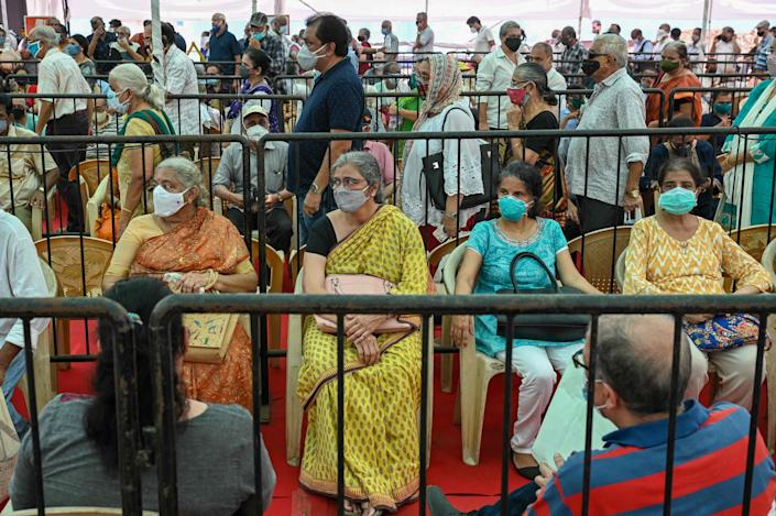 People line up to receive a dose of a COVID-19 vaccine at a vaccination center in Mumbai, India on Tuesday.