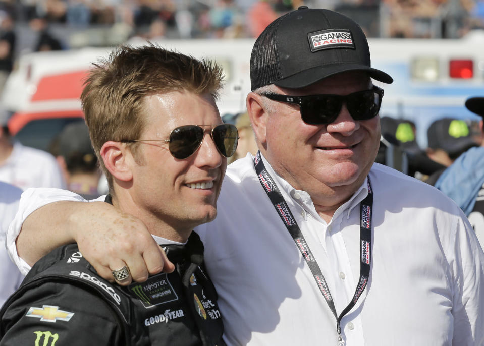 """FILE - Jamie McMurray, left, and car owner Chip Ganassi greet each other on pit road before a NASCAR Daytona 500 auto race at Daytona International Speedway, in Daytona Beach, Fla., in this Sunday, Feb. 17, 2019, file photo. Ganassi won the Daytona 500 and the Brickyard 400, two of the biggest races in NASCAR, with McMurray in 2010. Chip Ganassi has sold his NASCAR team to Justin Marks, owner of Trackhouse Racing, and will pull out of the nation's top stock car series at the end of this season. Ganassi fields two cars in the Cup Series but will transfer his North Carolina race shop and all its assets to Marks for 2022. """"He made me a great offer that required my attention,"""" Ganassi told The Associated Press on Wednesday, June 30, 3031, as the sale was announced. (AP Photo/Terry Renna, File)"""