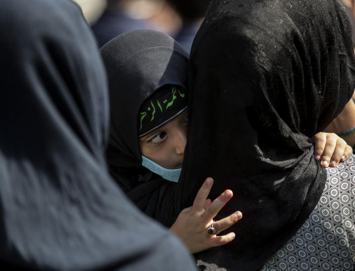 A young Kashmiri Shiite Muslim watches a Muharram procession, cradled in the arms of a woman in Srinagar, Indian controlled Kashmir, Saturday, Aug. 29, 2020. Muharram is a month of mourning in remembrance of the martyrdom of Imam Hussein, the grandson of Prophet Mohammed. Authorities had imposed restrictions in parts of Srinagar, the region's main city, to prevent gatherings marking Muharram from developing into anti-India protests. (AP Photo/Mukhtar Khan)
