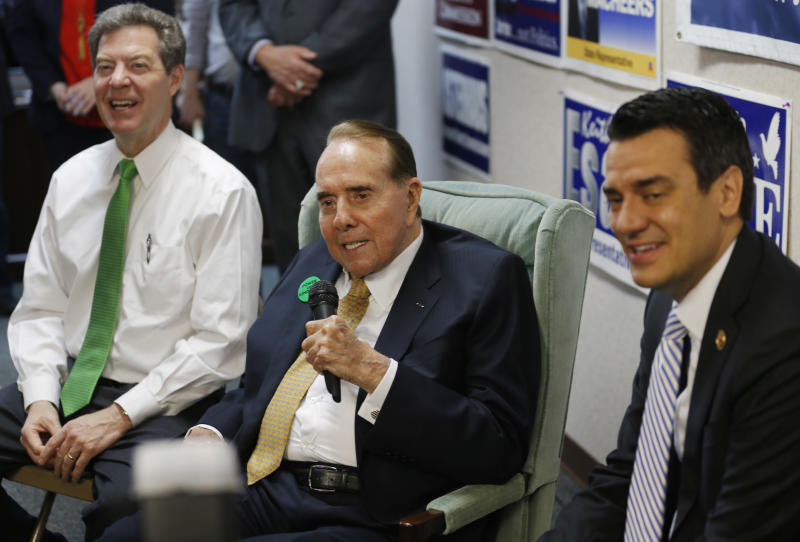 Former Sen. Bob Dole, R-Kan., center, takes questions while seated between Gov. Sam Brownback, left, and Rep. Kevin Yoder, R-Kan., right, during a visit to the Johnson County Republican Headquarters in Overland Park, Kan., Monday, April 21, 2014. (AP Photo/Orlin Wagner)