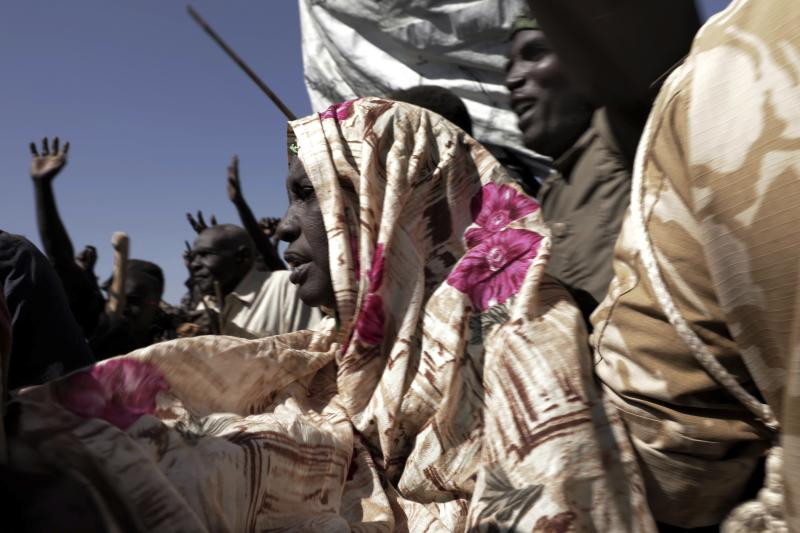 People chant slogans during a visit organized by The World Food Program (WFP) in the conflict-affected remote town of Kauda, Nuba Mountains, Sudan, Jan. 9, 2020. Sudan's Prime Minister, Abdalla Hamdok, accompanied by United Nations officials, embarked on a peace mission Thursday to Kauda, a rebel stronghold, in a major step toward government efforts to end the country's long-running civil conflicts. (AP Photo/Nariman El-Mofty)