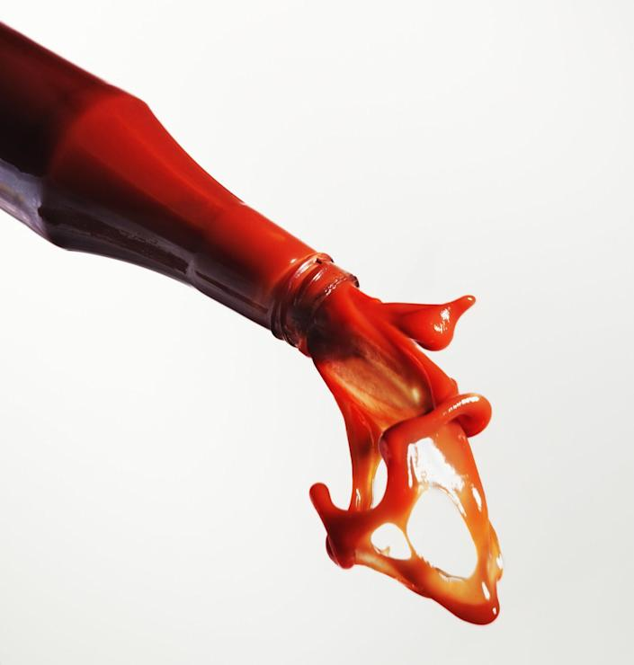 Side view of a bottle pouring out ketchup