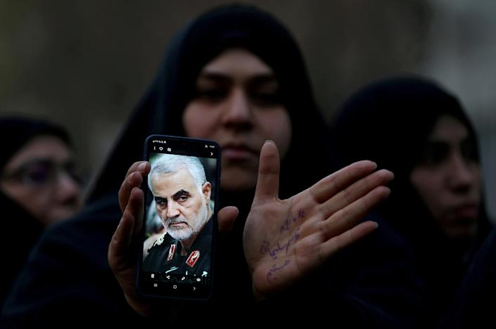 An Iranian woman shows a photo of Soleimani during a protest against his killing in front of the United Nations office in Tehran, Iran, on Jan. 3, 2020. (Nazanin Tabatabaee/West Asia News Agency via Reuters)