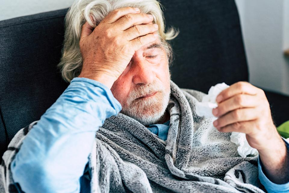 A senior man sits on a couch wrapped in a blanket while touching his forehead and feeling for a fever, suffering from COVID symptoms