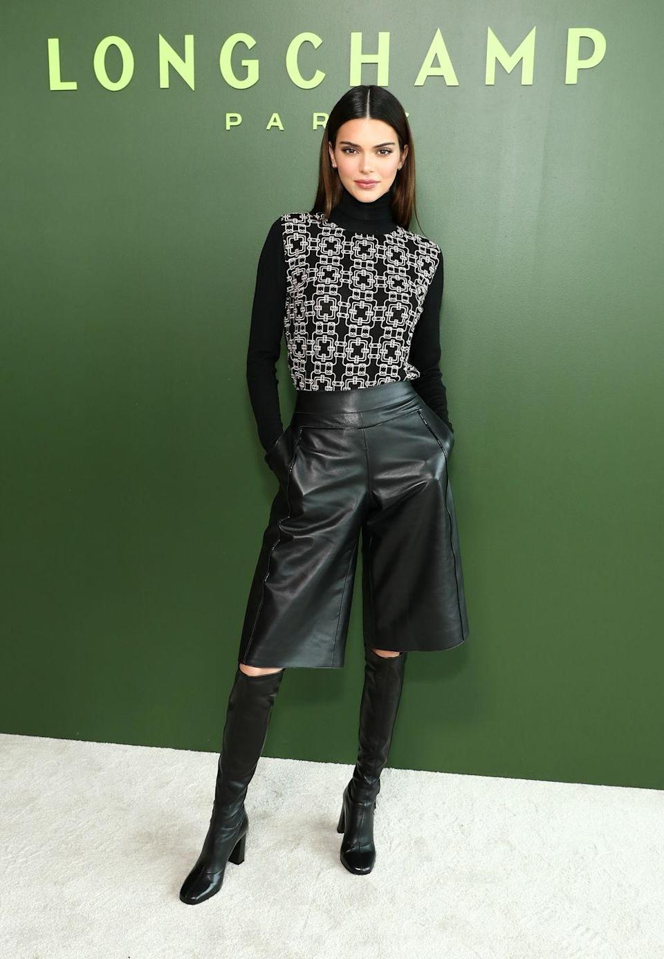 """<p>Model Kendall Jenner attended Longchamp's AW2o show in New York wearing over-the-knee boots and a patterned turtle neck.</p><p>The 24-year-old successfully nailed one of the trickiest trends out there right now, leather <a href=""""https://www.elle.com/uk/fashion/articles/g18182/leather-shorts/"""" rel=""""nofollow noopener"""" target=""""_blank"""" data-ylk=""""slk:bermuda shorts"""" class=""""link rapid-noclick-resp"""">bermuda shorts</a>.</p><p><a class=""""link rapid-noclick-resp"""" href=""""https://go.redirectingat.com?id=127X1599956&url=https%3A%2F%2Fwww.stories.com%2Fen_gbp%2Fclothing%2Fshorts%2Fproduct.leather-culotte-shorts-black.0814449001.html&sref=https%3A%2F%2Fwww.elle.com%2Fuk%2Ffashion%2Fcelebrity-style%2Farticles%2Fg2543%2Fkendall-jenner%2F"""" rel=""""nofollow noopener"""" target=""""_blank"""" data-ylk=""""slk:SHOP LEATHER BERMUDA SHORTS"""">SHOP LEATHER BERMUDA SHORTS</a></p>"""