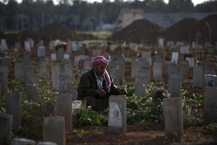 A Syrian man prays over the grave of his son, who was killed during shelling, at a cemetery in the rebel-held Damascus suburb of Douma, on March 5, 2015 (AFP Photo/Abd Doumany)