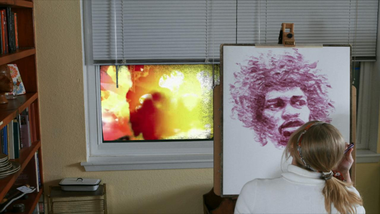 Natalie Irish works on her portrait of Jimi. Videos on the artist's website show her entire fascinating process and incorporate other artistic elements - as you can see in the window pane here.  (Photo: Chris O'Malley)