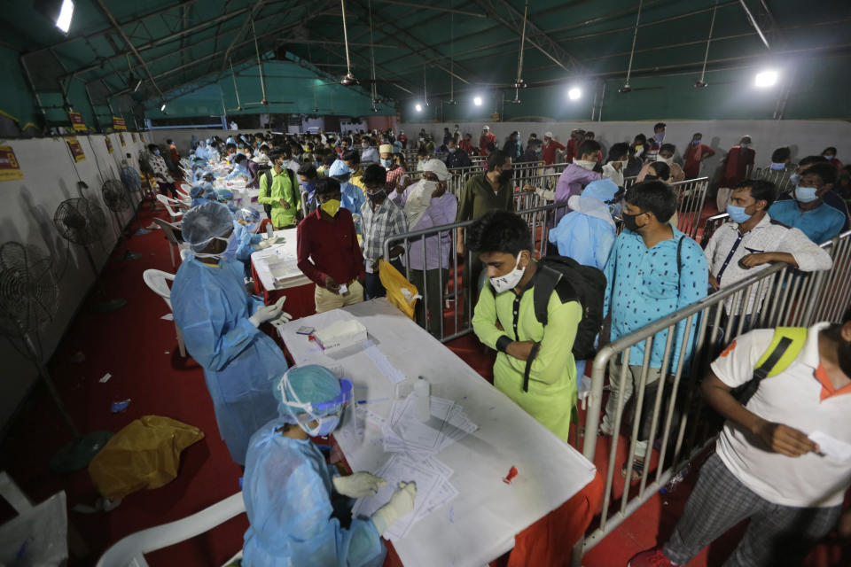 Indian passengers queue up to test for COVID-19 at a facility erected at a railway station to screen people coming from outside the city, in Ahmedabad, India, Friday, Sept. 18, 2020. India's coronavirus cases jumped by another 96,424 in the past 24 hours, showing little sign of leveling. India is expected to have the highest number of confirmed cases within weeks, surpassing the United States, where more than 6.67 million people have been infected. (AP Photo/Ajit Solanki)