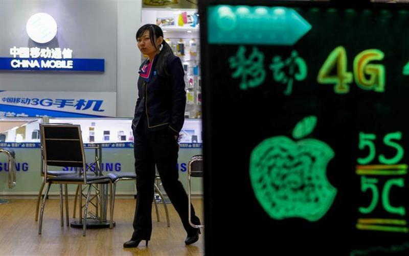 A sales assistant walks inside a China Mobile store in Guangzhou, Guangdong province, December 18, 2013.