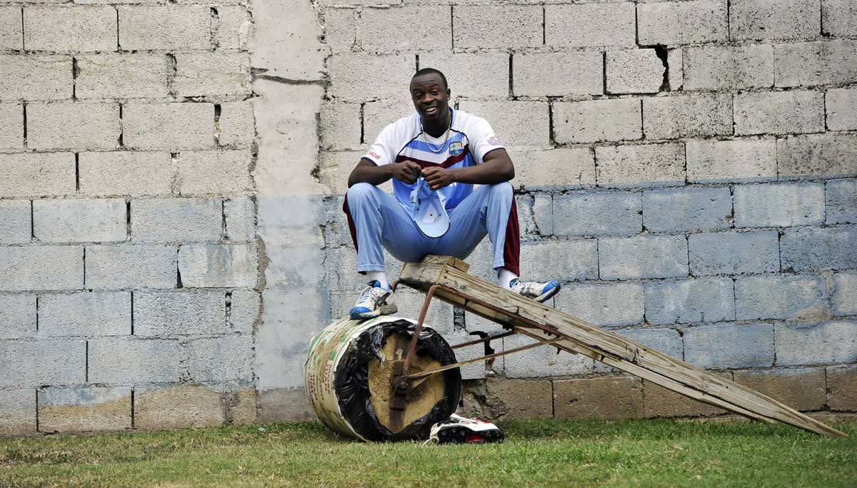 West Indies cricketer Kemar Roach watches teammates practicing during a session at the Sabina Park stadium in Kingston on June 27, 2013. West Indies will face Sri Lanka in the first match of a Tri Nation series involving India too. AFP PHOTO/Jewel Samad