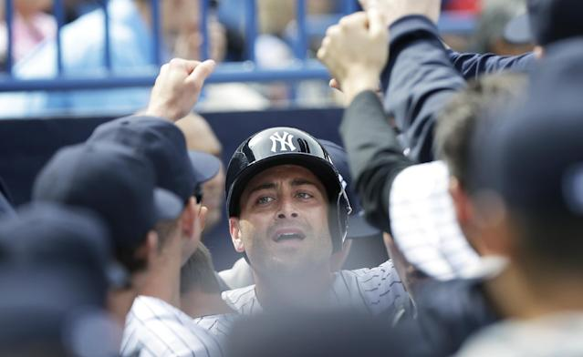 New York Yankees catcher Francisco Cervelli, center, celebrates with teammates after scoring a run during the fifth inning of an exhibition baseball game against the Pittsburgh Pirates Thursday, Feb. 27, 2014, in Tampa, Fla. (AP Photo/Charlie Neibergall)