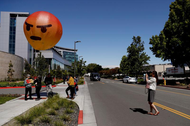 A passerby takes a photograph of an inflatable angry emoji during a protest outside the Facebook 2019 Annual Shareholder Meeting in Menlo Park, California