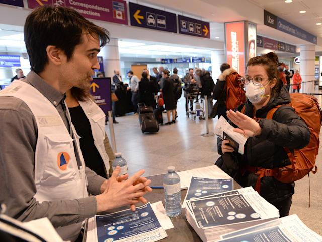 A Quebec health worker, assigned by the city of Montreal, greets a passenger and hands out information on COVID-19 at Trudeau Airport in Montreal, Monday, March 16, 2020. THE CANADIAN PRESS/ Ryan Remiorz