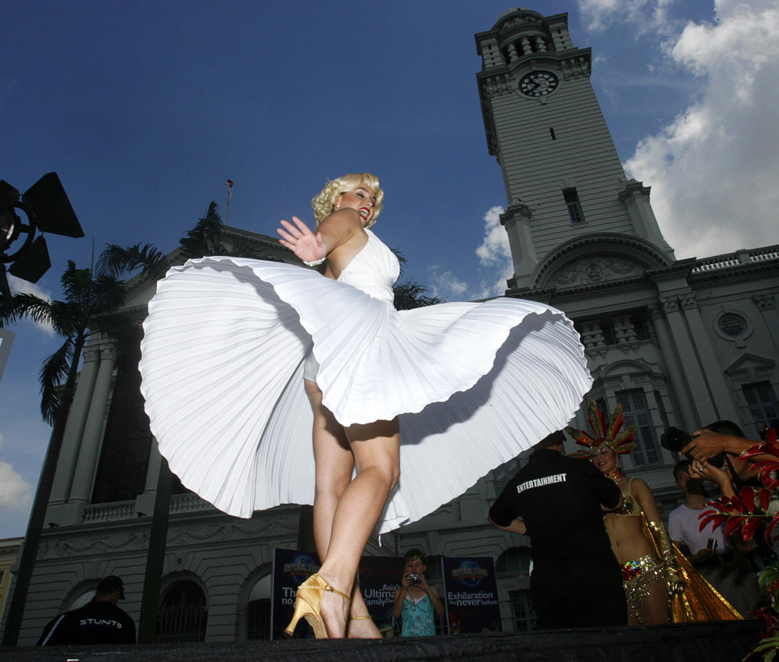 Actress dressed in Marilyn Monroe costume poses for photographers in front of Victoria Theatre in Singapore Vivek Prakash / Reuters