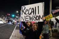 FILE - In this Nov. 21, 2020, file photo, demonstrators shout slogans while carrying a sign calling for a recall on Gov. Gavin Newsom during a protest against a stay-at-home order amid the COVID-19 pandemic in Huntington Beach, Calif. Organizers of the recall effort against Gov. Newsom collected enough valid signatures to qualify for the ballot. The California secretary of state's office announced Monday, April 26, 2021 that more than 1.6 million signatures had been verified, about 100,000 more than needed to force a vote on the first-term Democrat. (AP Photo/Marcio Jose Sanchez, File)