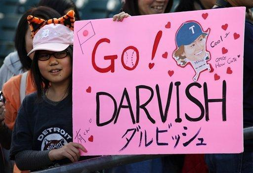 Kanon Furuyama, 10, of Detroit, holds up a sign for Texas Rangers pitcher Yu Darvish before a baseball game against the Detroit Tigers in Detroit, Thursday, April 19, 2012. (AP Photo/Paul Sancya)