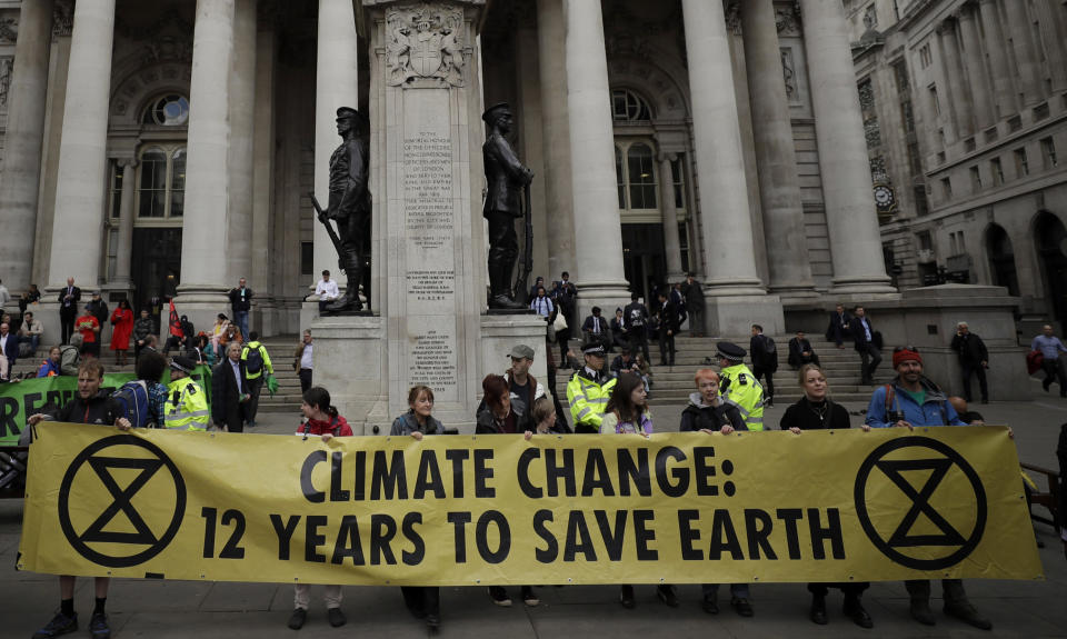"FILE - In this Thursday, April 25, 2019 file photo, Extinction Rebellion climate change protesters hold up a banner near the Bank of England, in the City of London. The environmental activist group Extinction Rebellion has postponed a plan to shut down London's Heathrow Airport with drones after it was criticized by politicians and police. The anti-climate change group said Sunday, June 16 it would ""not be carrying out any actions at Heathrow Airport in June or July."" (AP Photo/Matt Dunham, file)"