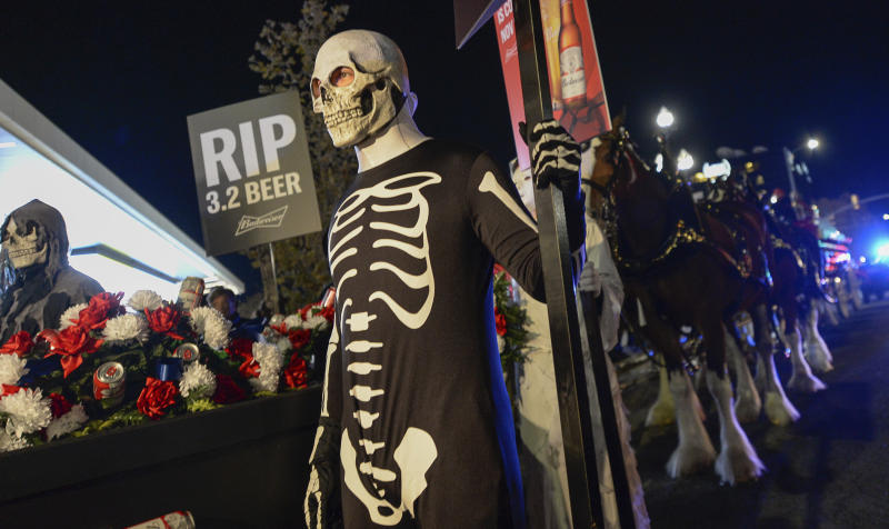 """A """"funeral"""" procession for Utah's last remaining 3.2 percent beer, complete with Budweiser's iconic Clydesdales, background right, makes its way en route to Bar X, Beer Bar and Johnny's on 200 South in Salt Lake City, Wednesday, Oct. 30, 2019, to celebrate the changing beer laws in the state. Utah prepares to start selling a higher percentage alcohol-by-volume in grocery and convenience stores starting Friday. (Francisco Kjolseth"""