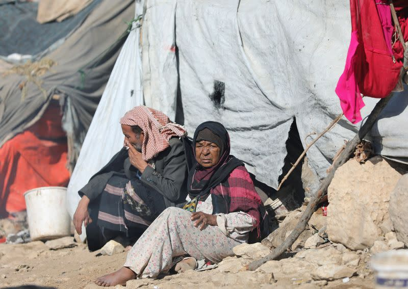 People sit in the sun on a cold winter day at a camp for internally displaced people in Khamir of the northwestern province of Amran