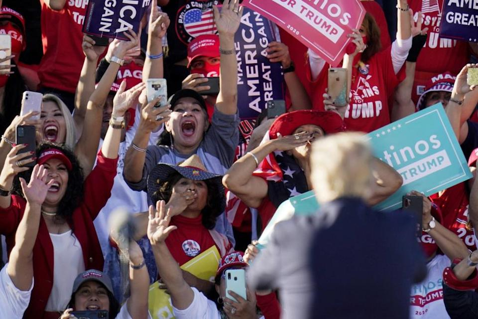 Donald Trump acknowledges the cheering crowd behind him at a campaign rally in Goodyear, Arizona, on 28 October.