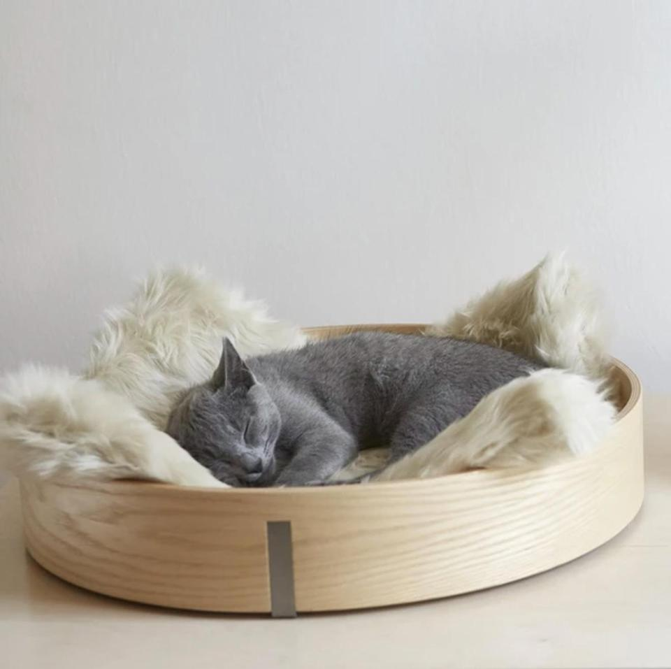 """<p>Minimalist design enthusiasts rejoice! We have found the cat bed for you. This sleek circular basket features a clean-lined natural wood frame and machine-washable faux fur cushion that even the pickiest of cat parents won't mind showing off in plain sight.</p> <p><strong><em>Shop Now:</em></strong><em> MiaCara Anello Cat Basket, in Ash/Ivory, $199, </em><a href=""""https://landofmeow.com/products/anello-cat-basket-ash-ivory"""" rel=""""nofollow noopener"""" target=""""_blank"""" data-ylk=""""slk:landofmeow.com"""" class=""""link rapid-noclick-resp""""><em>landofmeow.com</em></a><em>.</em></p>"""