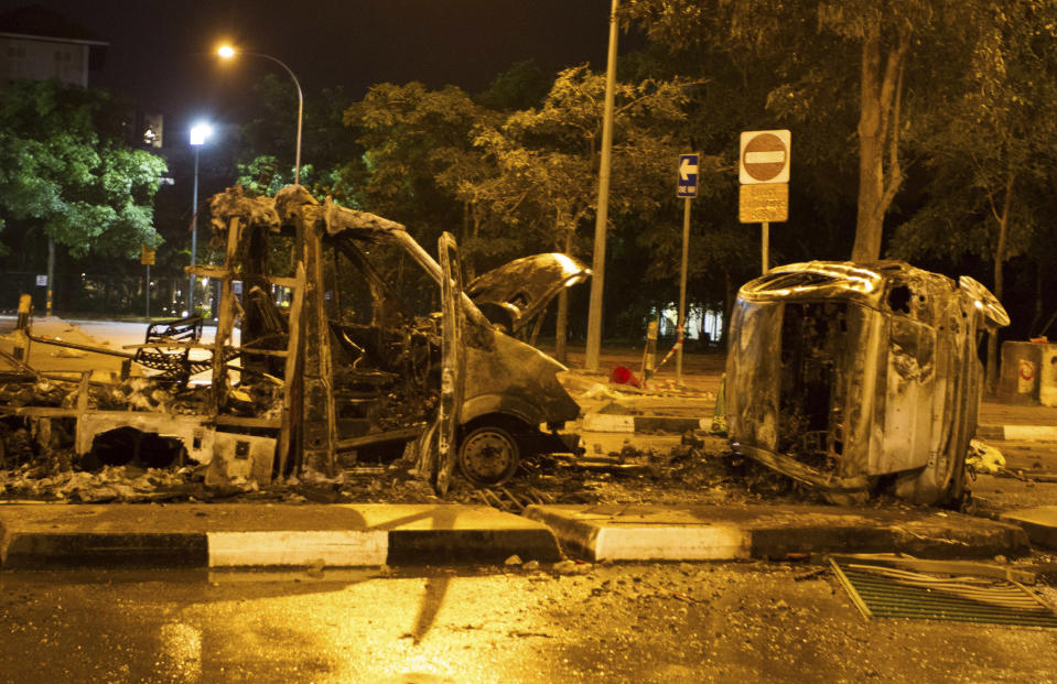 The burnt shells of vehicles are pictured along Race Course Road following a riot near Singapore's Little India district December 9, 2013. Local media said a mob of about 400 set fire to an ambulance and police cars during the riot on Sunday, which started after a bus knocked down a pedestrian. REUTERS/Stringer (SINGAPORE - Tags: CIVIL UNREST)