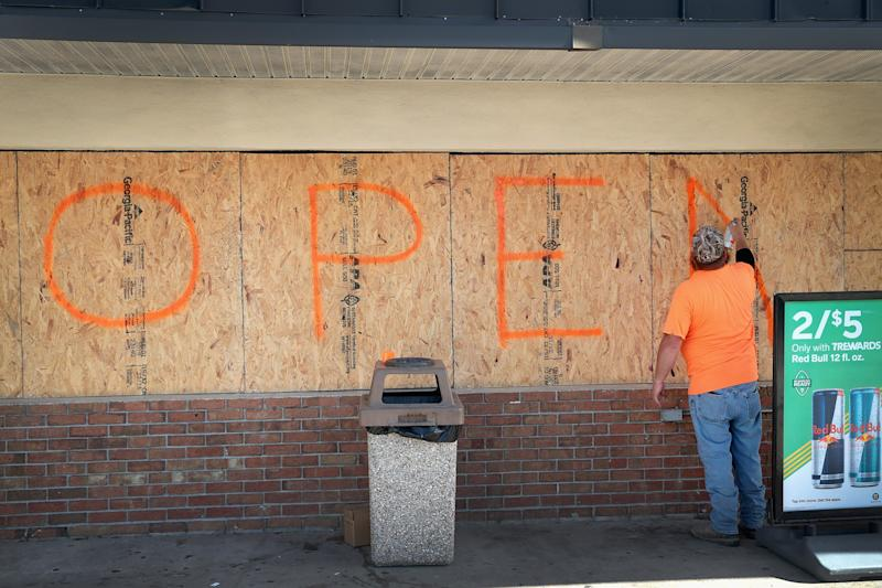 A man boards up the windows of his store in Florida in preparation for Hurricane Dorian (Picture: Getty)