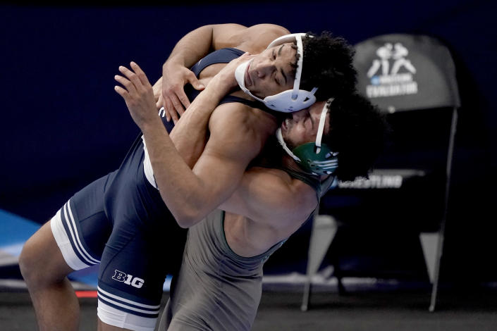 Penn State's Carter Starocci, left, is life up by Utah Valley's Demetrius Romero during their 174-pound match in the semifinal round of the NCAA wrestling championships Friday, March 19, 2021, in St. Louis. (AP Photo/Jeff Roberson)