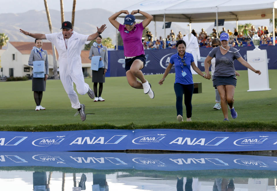 """FILE - Lydia Ko, of New Zealand, in pink, forms a heart as she jumps into Champions Lake, or """"Poppie's Pond,"""" alongside her caddie, Jason Hamilton, left, after winning the LPGA Tour ANA Inspiration golf tournament at Mission Hills Country Club in Rancho Mirage, Calif., in this Sunday, April 3, 2016, file photo. The longtime major is leaving for the Houston area in 2023 under a new sponsorship with Chevron. (AP Photo/Gregory Bull, File)"""