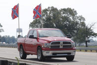 A truck flying Confederate flags passes by the Talladega Superspeedway prior to the NASCAR Cup Series auto race at the in Talladega Ala., Sunday June 21, 2020 (AP Photo/John Bazemore)