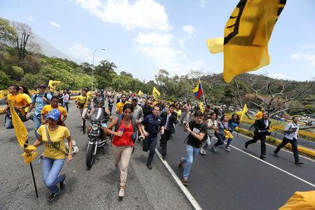 Opposition supporters run as they block a highway during a protest against Venezuela's President Nicolas Maduro's government in Caracas