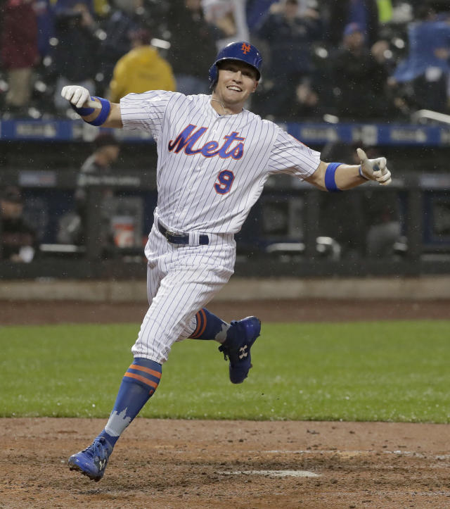 New York Mets' Brandon Nimmo (9) celebrates as he crosses the plate to score the winning run on a sacrifice fly ball by Wilmer Flores during the ninth inning of a baseball game against the Arizona Diamondbacks, Saturday, May 19, 2018, in New York. (AP Photo/Julie Jacobson)