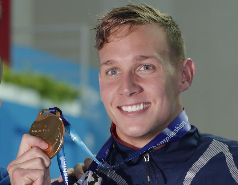 File-This July 27, 2019, file photo shows gold medalist United States' Caeleb Dressel posing with his gold medal following the men's 50m freestyle final at the World Swimming Championships in Gwangju, South Korea. In the post-Michael Phelps world, Dressel fits snugly into the successor's slot. Coming off two dynamic performances at the world swimming championships, Dressel figures to be one of the biggest stars at the 2020 Tokyo Games.  Yet he is reticent to step into the spotlight. (AP Photo/Lee Jin-man, File)