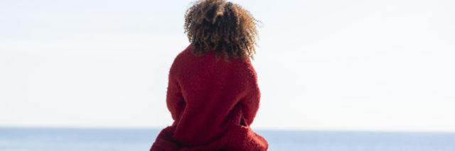 Woman with curly hair sitting on a bench at the beach.