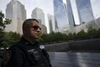 """NYPD officer Michael Dougherty, a 25-year veteran, stands beside the south reflecting pool of the 9/11 Memorial & Museum where names of his deceased colleagues and friends are displayed, Monday, Aug. 16, 2021, in New York. Dougherty's first professional experience with the World Trade Center was as an electrician. """"It's a privilege to be here,"""" said Dougherty. """"I'm at the end of my career and I couldn't think of a better place for me to finish up, connect where I started my career as an electrician over twenty five years ago before I became a police officer, and end up here. To be the guardian of this area and look over all my friends and family that passed away here 20 years ago."""" (AP Photo/John Minchillo)"""